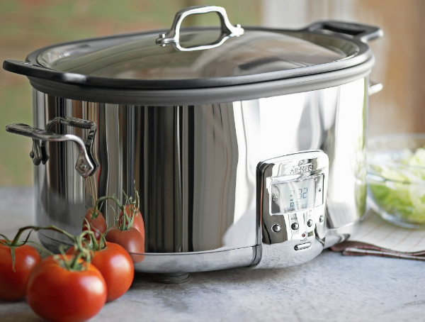 Cool-interior-design-featuring-stainless-slow-cooker-on-cabinet-put-beside-tomato-and-glass-bowl